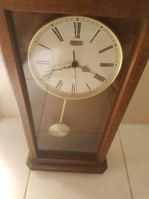 Reloj antiguo de pared hecho de madera con péndulo