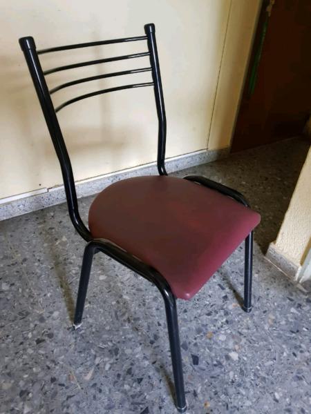 Mesa de madera con 4 sillas de fierro.