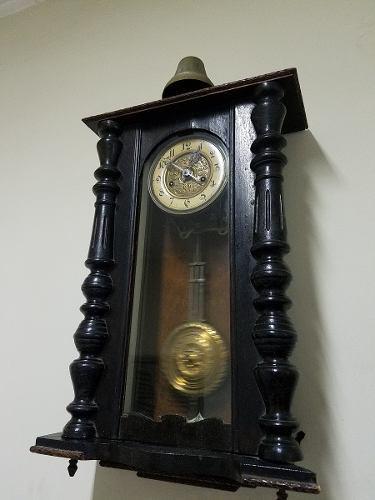 Reloj antiguo de pared pendulo funcionando con campana