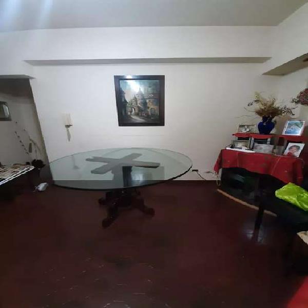 Mesa redonda de vidrio con pies de algarrobo